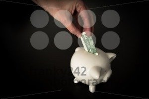 Woman putting a US Dollar bank note into a piggy bank - franky242 photography