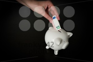 Woman putting a ten Euro bank note into a piggy bank - franky242 photography