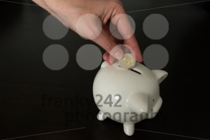 Woman putting two Euro coin into a piggy bank - franky242 photography