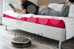 Vacuum cleaning robot with relaxed woman reading in the background - franky242 photography