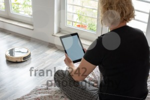 Vacuum cleaning robot with woman reading - franky242 photography
