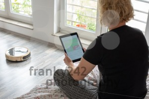 Woman is steering her vacuum cleaning robot from the bed - franky242 photography