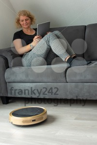 Woman is steering her vacuum cleaning robot from the sofa - franky242 photography