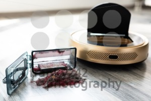 robotic vacuum cleaner on wood floor with emptied dirt container - franky242 photography