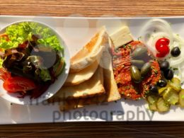 Steak tartare served with side dishes, toast and salad