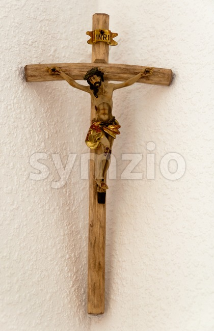 A wooden crucifix  mounted in the corner of a living room