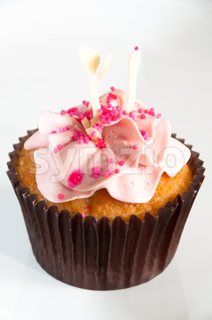 Beautiful cupcake decorated with frosting and dragees