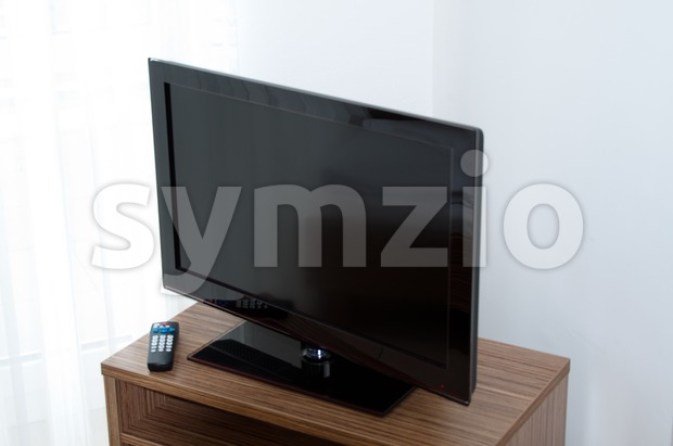 Flatscreen TV on wooden rack with remote control