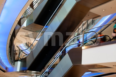 People On Escalator In Modern Shopping Mall Stock Photo
