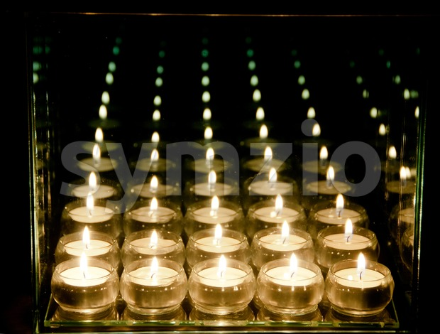 Candles and their reflections in glass frame