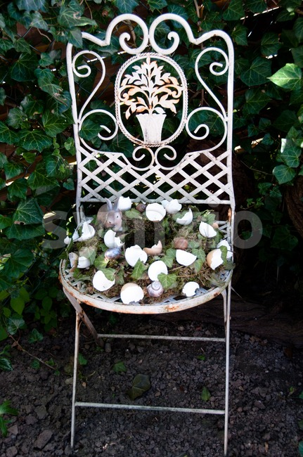 Easter Egg Wreath Decoration On Old Chair in Garden