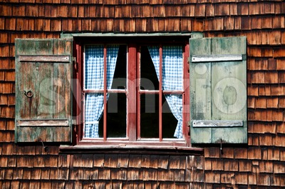 Ancient window on log house wooden wall Stock Photo