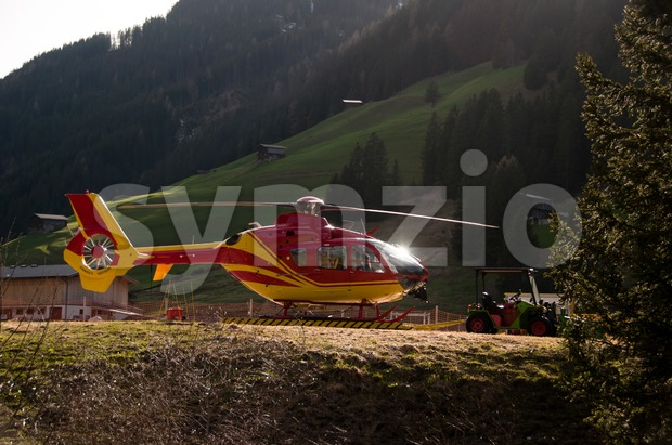 Grounded Yellow and Red Helicopter At Hangar Stock Photo