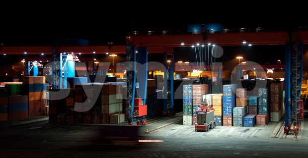 Busy Commercial Container port at night with cranes and cars moving containers