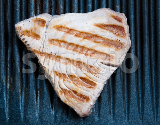 Tuna fish steak cooking on a grill