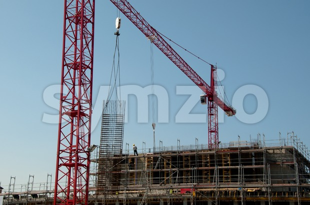 Construction site with red cranes and building