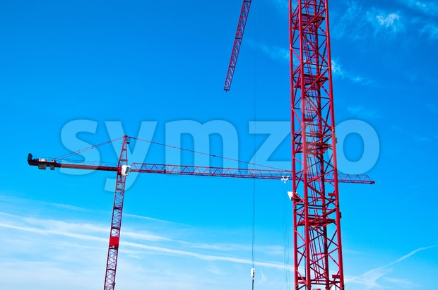Closeup of two red tower construction cranes against blue sky