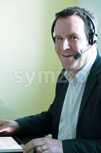 Businessman with digital tablet PC and headset Stock Photo
