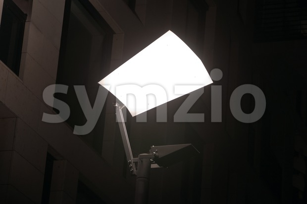 Closeup of brightly lit streetlight with reflector