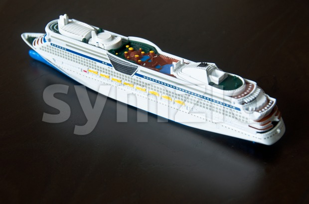 Miniature model of a cruise ship (childrens toy) on wooden table