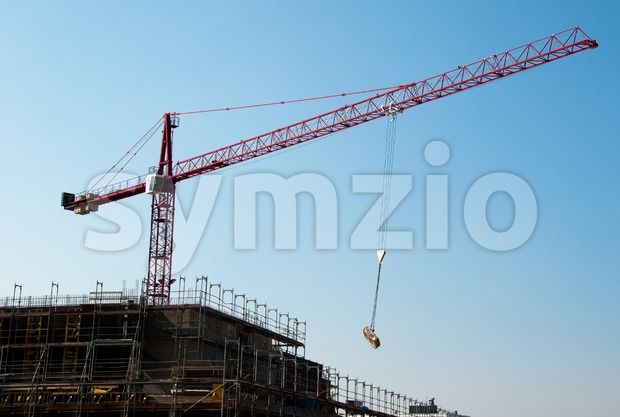 Construction site with red crane and building