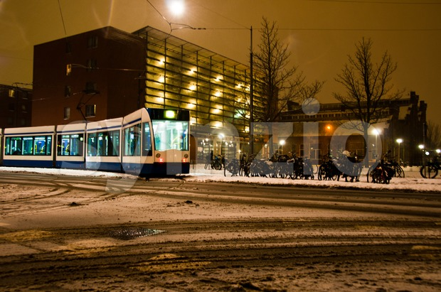 A public Tram driving in Amsterdam during a snowy night