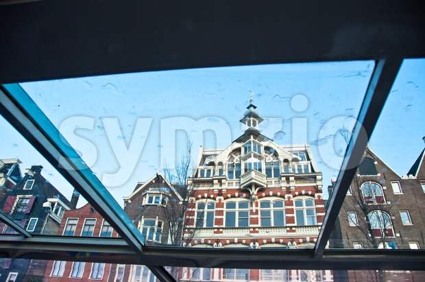 Amsterdam houses through the window of a canal boat