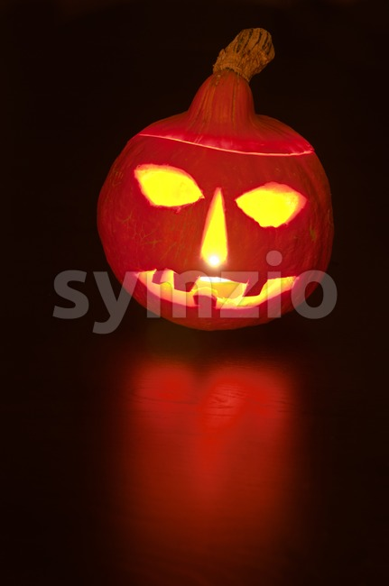 Scary Halloween Pumpkin lit by candle with reflection on dark wooden table..