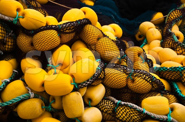 Closeup on fishing net with yellow floaters stored on fisher boat during the day