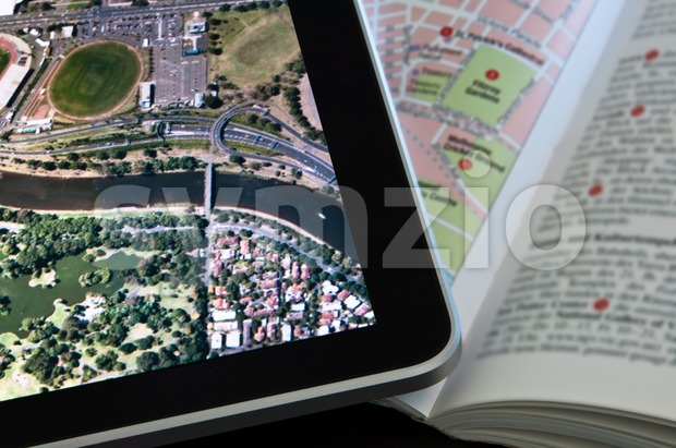 Modern Tablet PC displaying a city map with classic printed travel guide next to it