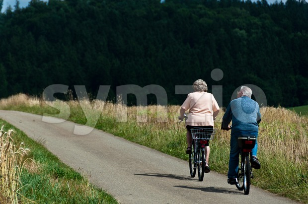 Elderly couple cycling on pavement between cornfields and forest