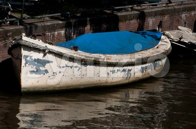 Very old boat in canal in Amsterdam, Netherlands Stock Photo
