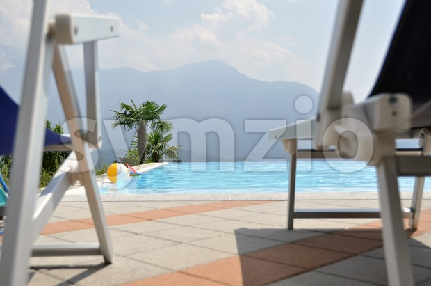 Pool and palms with chairs Stock Photo