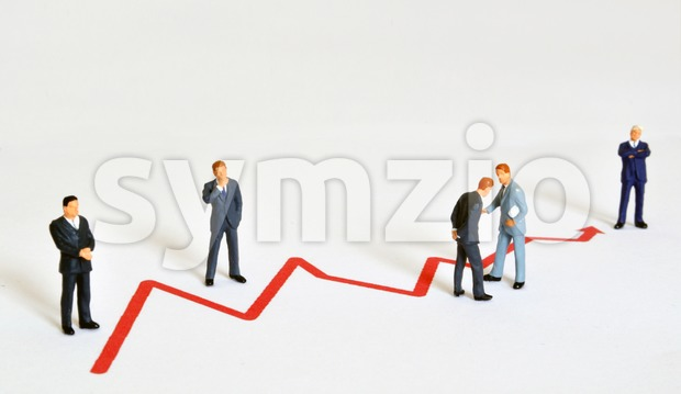 Group of managers (model railroad figures) positiones around graph showing rising business development.