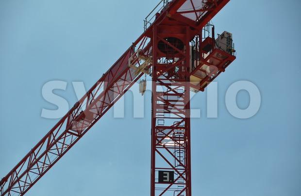 Closeup of a red tower construction crane against blue sky..