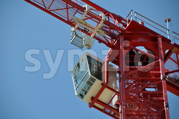Detail of a red tower construction crane against blue sky..