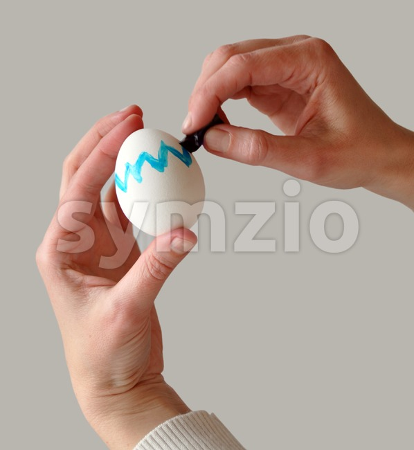 Female hands coloring an easter egg with gray background that is easy to remove