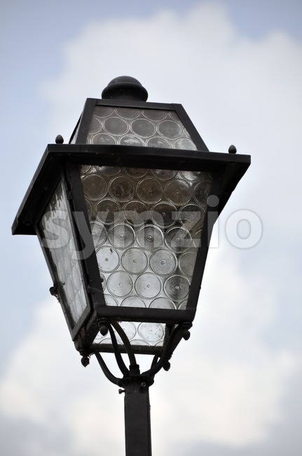 Closeup of an old street light in front of bright and cloudy sky..