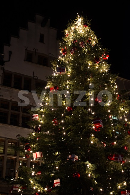 Christmas tree at night, in front of beautiful old building