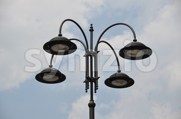 Closeup of an old  fashioned street lamp  in front of bright and cloudy sky