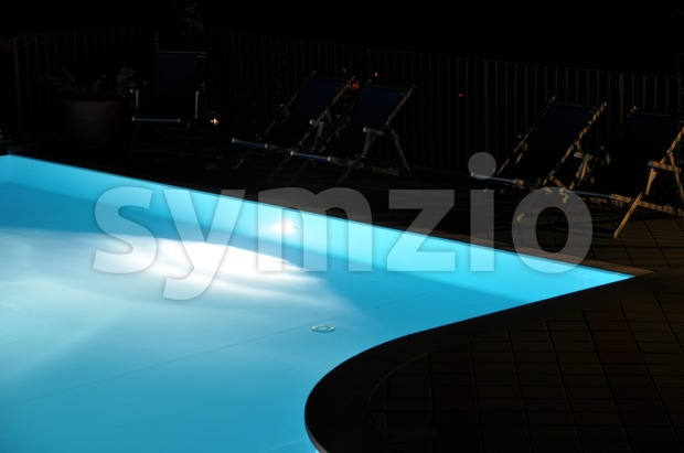 Image of an illuminated pool at night with chairs