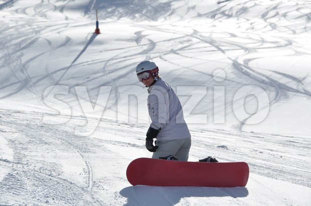 Female snowboarder kneeling in powder snow Stock Photo