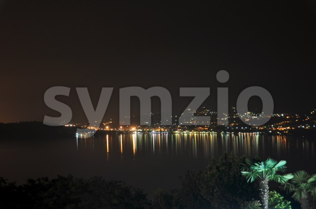 Nightly view over the Lake Como on Colico with brightly lit palm tree in the foreground