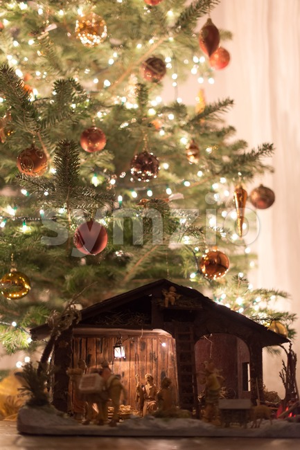 Beautifully decorated christmas tree with large wooden crib