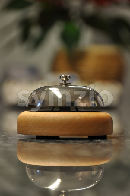Detail shot of a service bell located on a hotel reception desk with blurred details in the background and reflection ...