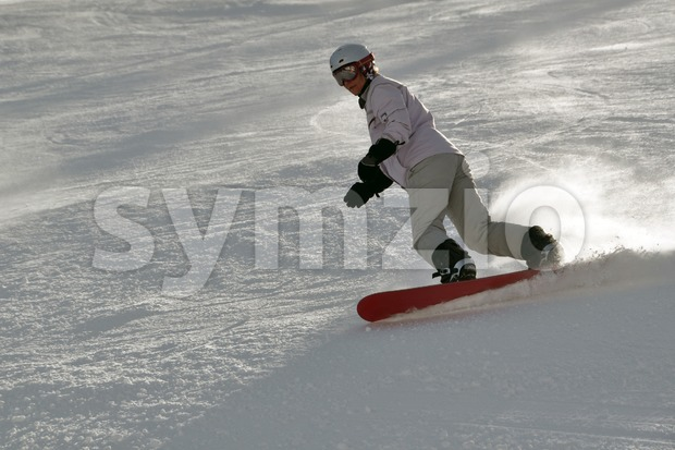 Middle aged female snowboarder wearing helmet and snow goggles in powder snow on steep hill - shot in Livigno, Italian ...