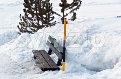 Snow covered bench and snow pole Stock Photo