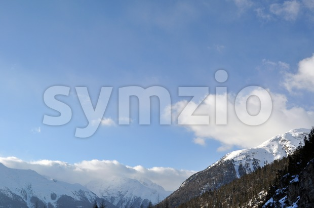 Mountain panorama, covered with trees and high snow, partly in the clouds. Shot in Livigno - Italian Alps