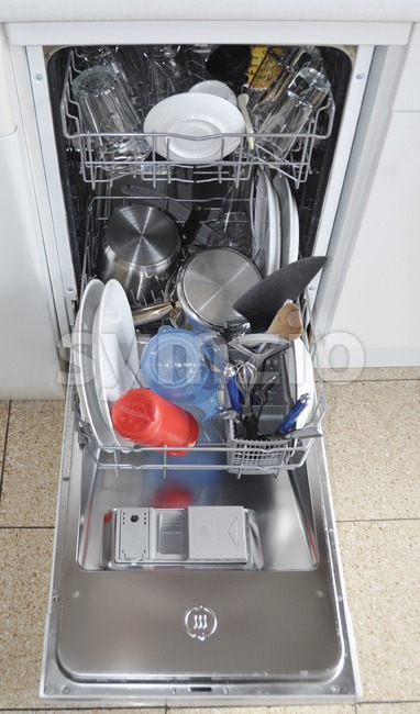 Dishwasher with open hatch and clean dinnerware Stock Photo