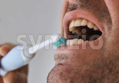 Man brushing his teeth with electric toothbrush Stock Photo